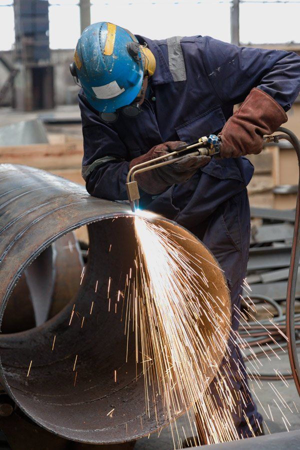 expert cutting a steel pipe with a gas cutter