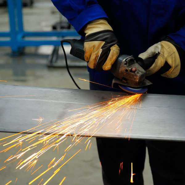 welder smoothing the edges with the help of a machine